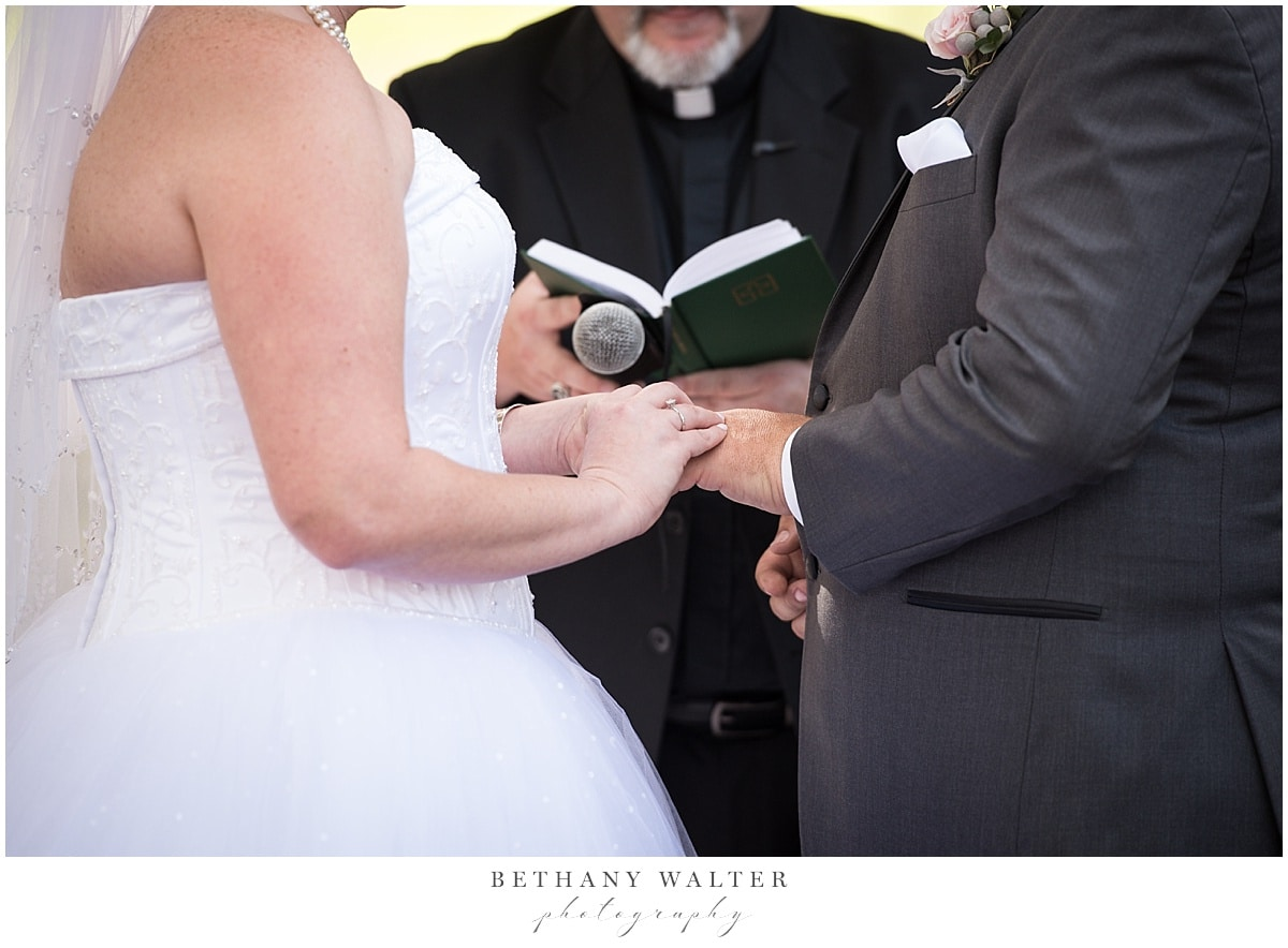 Bride and groom exchanging rings during their ceremony at Plantation Oaks