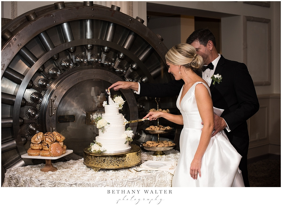 Bride and Groom Cutting the Wedding Cake in Front of the Vault Bar