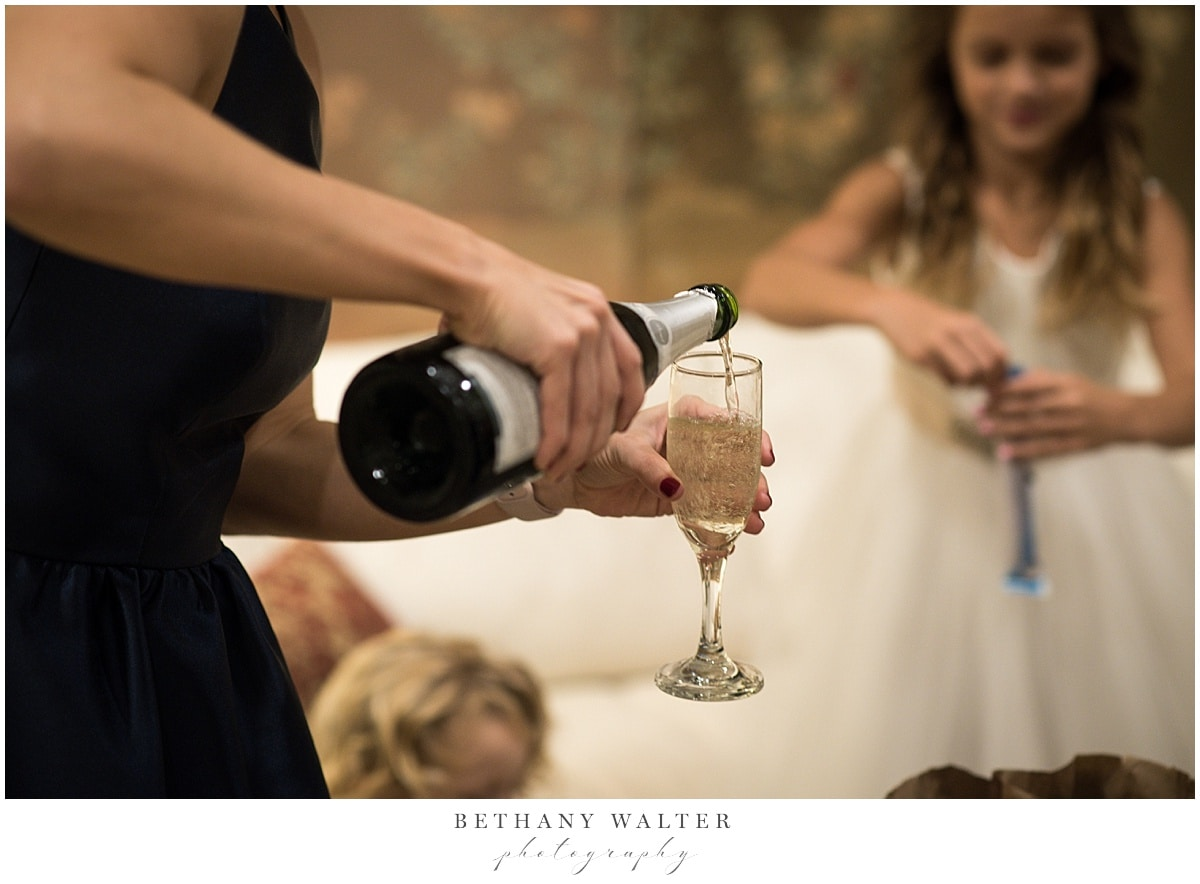 Maid of honor pour champagne in the bridal suite at Treasury on the Plaza